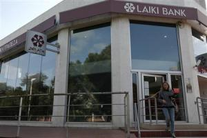 A woman walks out of a branch of Laiki Bank in Nicosia